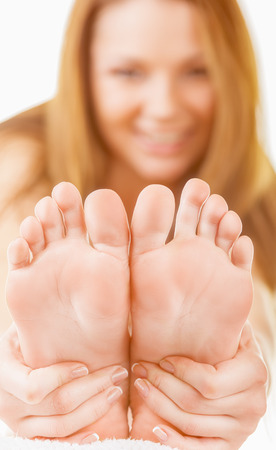 woman foot: Close-up woman applying moisturizer cosmetic cream on foot on light background. Focus on feet Stock Photo