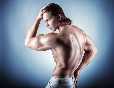 athletics: Strong athletic man back on a gray background Stock Photo