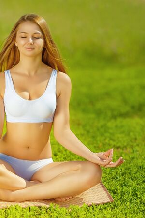 joga: Young beautiful woman in lotus pose on nature