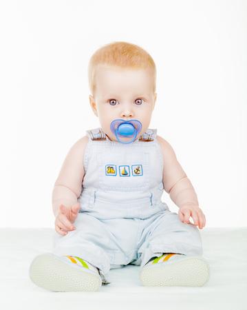 bebe sentado: hermoso bebé sentado en el suelo con un chupete aislado en el fondo blanco
