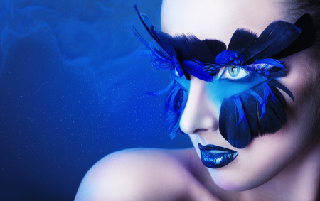 fantasy makeup: Mujer hermosa con maquillaje con plumas azules sobre un fondo azul