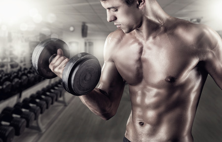powerfully: Close Up of a muscular young man lifting weights in the gym Stock Photo