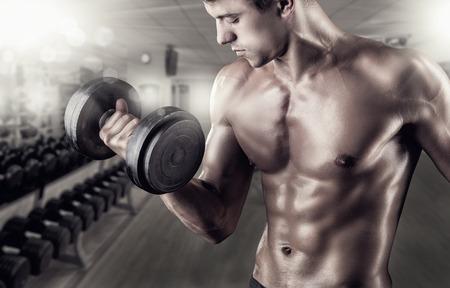 Close-up van een gespierde jonge man tillen gewichten in de sportschool