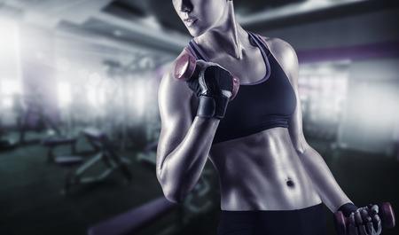 Close-up van een jonge vrouw te oefenen met gewichten in de sportschool Stockfoto