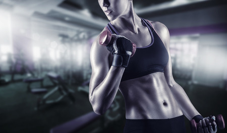 Close-up of a young woman exercising with weights in the gym Foto de archivo