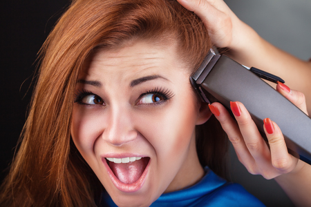 Young surprised woman at the hairdresser to cut your hair clippers Stock Photo