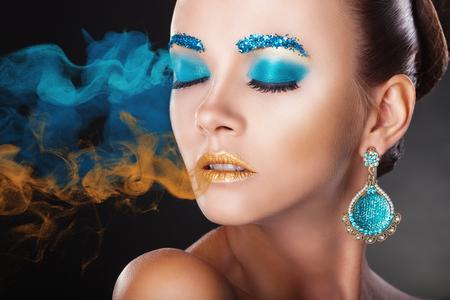 caritas pintadas: Mujer joven con maquillaje colorido de la moda con el humo multicolor