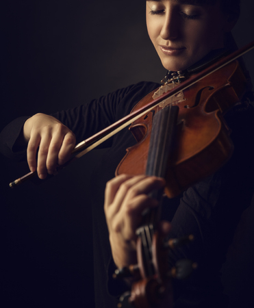 Beautiful young woman playing the violin on dark background Stock Photo