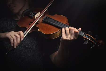 fiddle: Playing the violin. Musical instrument with performer hands on dark background