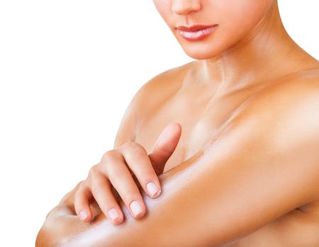 Close-up žena pečující o její paži použití kosmetického krému na bílém pozadí