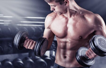 powerfully: Close up of a muscular young man lifting weights in gym