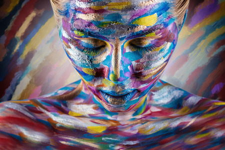 Young woman with colorful makeup and body art on a colorful background