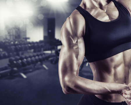 Close-up of a woman's body bodybuilder in the gym photo