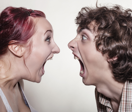 Close-up portrait of a pair of angry shouting against each other on a white background Standard-Bild