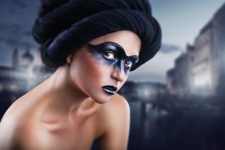 black makeup: Portrait of a young woman with a make-up black mask on the background of the city at night. Fashion make-up. Black mask