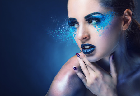 Close-up of a young woman with blue makeup on a dark blue background