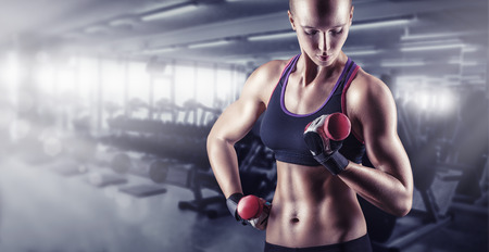 Training young sports woman in the gym with small weights Standard-Bild