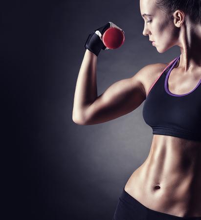 Dziewczyna fitness z hantlami na ciemnym tle