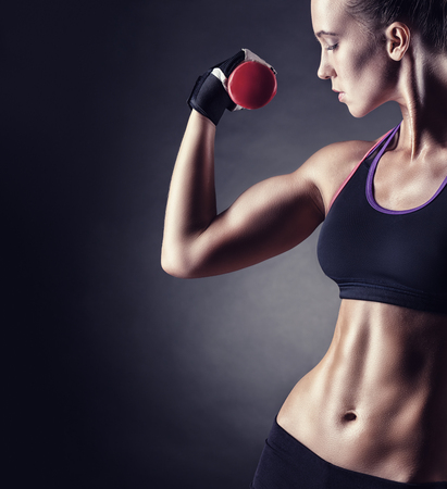 Fitness girl with dumbbells on a dark background Stock Photo - 62915872