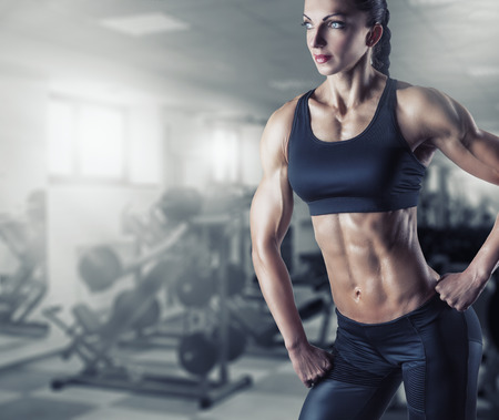 Beautiful athletic woman posing in the gym photo