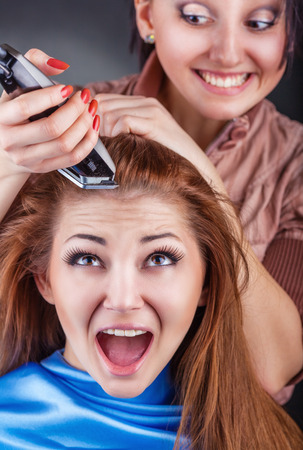 hairclipper: Young beautiful woman at the hairdresser cut their hair-clipper Stock Photo