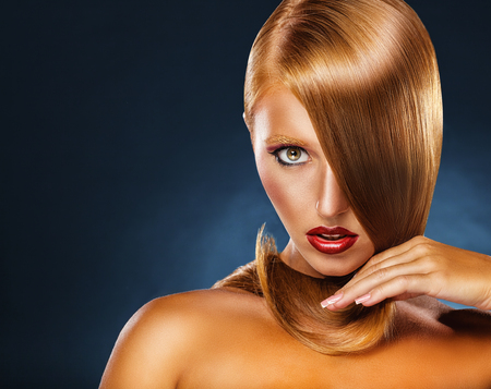 red lips: Portrait of a young red-haired woman on a blue background Foto de archivo