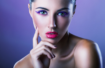 fashion background: Close-up of young woman with fashion makeup on a purple background Stock Photo