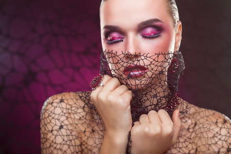 Beautiful young woman with fashion makeup and jewelry on a pink background Standard-Bild