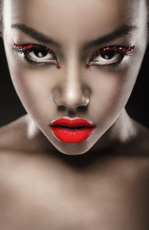 Close-up van een mooie zwarte vrouw met mode make-up, rode lippen. Glamoureus portret