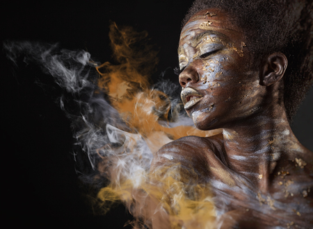 Young African American woman with silver and gold make-up and body art on a black background with smoke