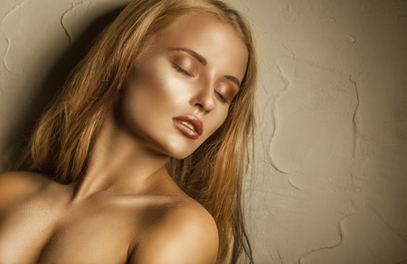 Beautiful young red-haired woman with golden make-up and closed eyes