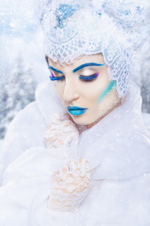 mystical: Snow queen with a bright blue make-up on a snowy background. Fashion makeup Stock Photo