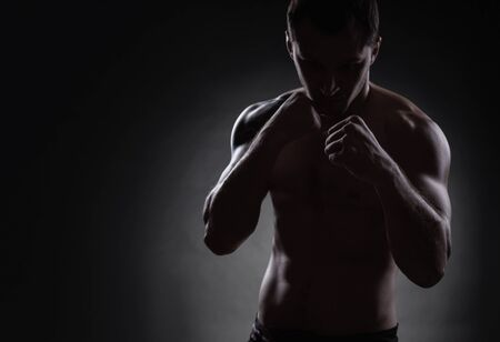 Fighter silhouette. Handsome athletic man in boxing stand on a dark background Stock Photo