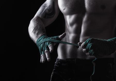 musculoso: Primer plano de un boxeador poner las correas que se preparan para el combate en un fondo oscuro Foto de archivo