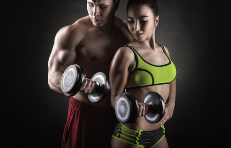 Fitness couple exercise with dumbbells on a black background Stock Photo