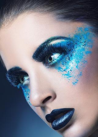 maquillaje de fantasia: Primer plano de una mujer joven con maquillaje azul sobre un fondo azul oscuro