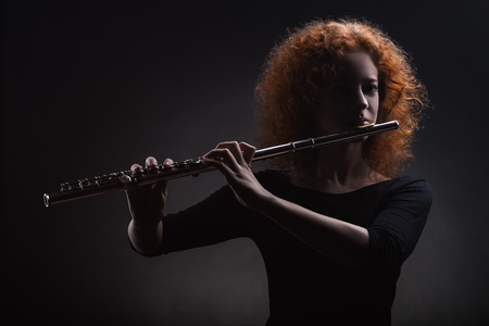 Young beautiful woman playing the flute on black background Stock fotó