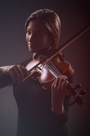 cellos: Beautiful young woman playing the violin on dark background Stock Photo
