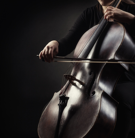 soloist: Close-up of cellist playing classical music on cello on black background Stock Photo