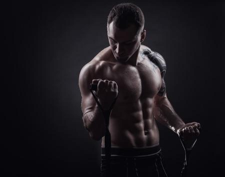 hombres negros: Concepto de los deportes. Apuesto joven ejercicio con goma contra un fondo oscuro
