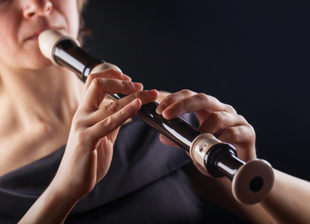 Close-up of a woman playing on a recorder on a black background