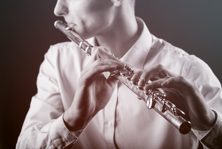 soloist: Young man playing the flute on black background