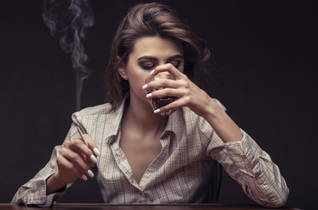 beautiful sad: Young beautiful woman is sad with a glass of red wine and a cigarette against a dark background