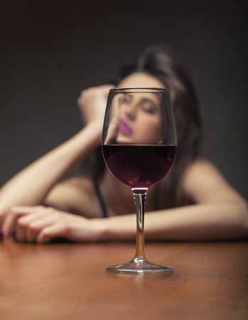 Woman in depression, drinking alcohol on dark background. Focus on the glass