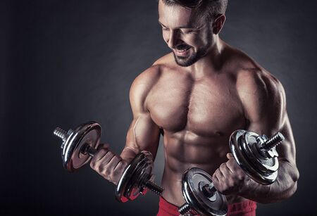 powerfully: Smiling fit muscular man exercising with dumbbell on dark background Stock Photo