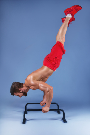 Strong male athlete shows calisthenic moves extended legs planche push ups on parallel bars, studio shot