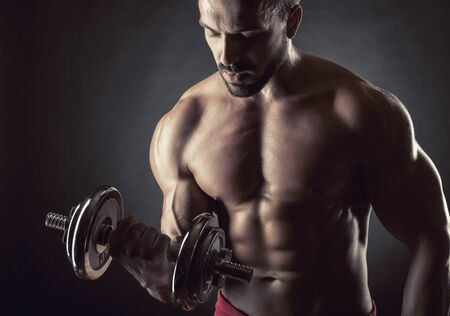 powerfully: Handsome muscular man exercising with dumbbell on dark background