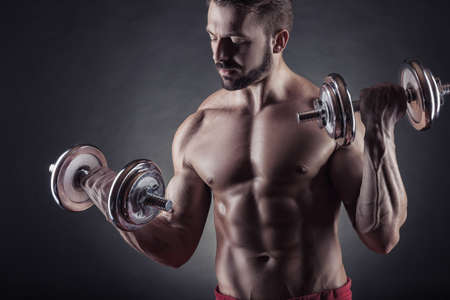 powerfully: Handsome smiling muscular man exercising with dumbbell on dark background
