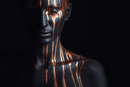 Art fashion makeup. An amazing woman with black makeup and leaking gold paint Stockfoto
