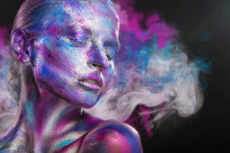 Fashion woman with colorful make-up and body art on a black background with multi-colored smoke
